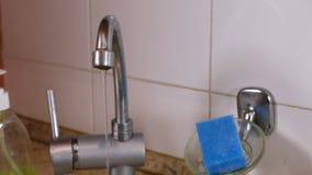 Vatten flödar i en tunn ström från klappet i köket Bruten vattenkran lager videofilmer