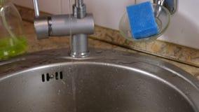 Vatten flödar i en tunn ström från klappet i köket Bruten vattenkran arkivfilmer