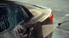 Vatten flödar på bilkropp under tvagningen, lokalvårdskum, närbildsikt arkivfilmer