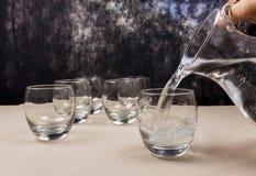 Vatten från en kanna hällde in i ett exponeringsglas Royaltyfri Bild