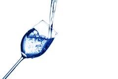 Vatten fylls in i ett exponeringsglas av vatten Arkivbild