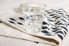 Vatten-fyllt dricka exponeringsglas på tabellservett med blåttfisken Desig Royaltyfria Foton