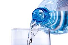 Vatten hällde från en plast- flaska in i ett exponeringsglas Fotografering för Bildbyråer