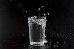 Vatten hälls in i dryckeskärlen på mörk bakgrund Arkivfoto