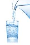 Vatten hällde från kannan in i ett exponeringsglas Royaltyfri Foto