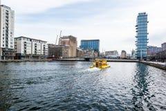 Vatten kantar med ett gult turist- kryssningfartyg/medel i mitten av Dublin fotografering för bildbyråer