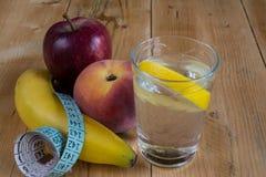 Vatten med citronen, frukter och mätaband Arkivbilder