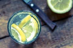 Vatten med citronen i ett exponeringsglas Royaltyfri Fotografi