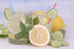 Vatten med citronen och gurka och mintkaramell i en glass kopp bredvid den nya citronen på en blå träbakgrund royaltyfri fotografi