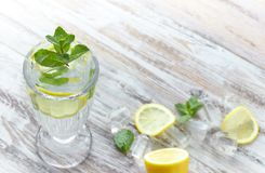 Vatten med citronen och mintkaramellen i en exponeringsglasbehållare på en trätabell placera text förnyande citrus drink för somm royaltyfria bilder