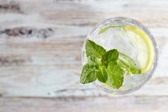 Vatten med citronen och mintkaramellen i en exponeringsglasbehållare på en trätabell placera text förnyande citrus drink för somm arkivfoto