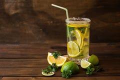 Vatten med limefrukt-, citron- och mintkaramellsidor på en mörk träbakgrund arkivbild