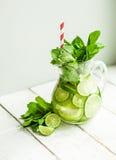Vatten med limefrukter och mintkaramellen på träbakgrund Royaltyfria Foton