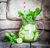 Vatten med limefrukter och mintkaramellen på träbakgrund Fotografering för Bildbyråer