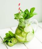 Vatten med limefrukter och mintkaramellen på träbakgrund Arkivfoto