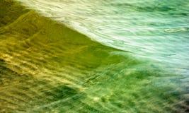 Vatten med mjuka vågor i gräsplan och guld Royaltyfria Foton