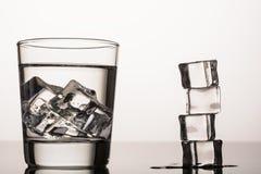 Vatten med is på vit bakgrund Arkivbild