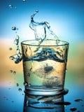 Vatten med is, sprej och färgstänk, en kall uppfriskande drink royaltyfria bilder