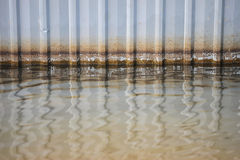 Vatten på golvet med den jämna fläckmodellen på rostig zink för gammal skada plat väggen arkivfoton