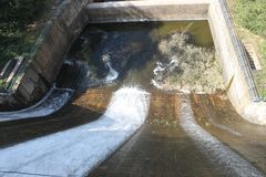 Vatten som försiktigt rusar ut ur porten på fördämningen Royaltyfri Foto