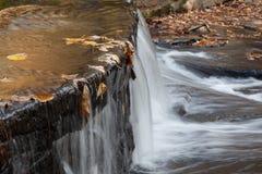 Vatten som faller över en fördämning Arkivfoto