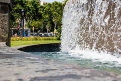 Vatten som faller från en springbrunn i en trädgård arkivfoton
