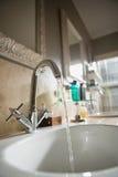 Vatten som faller från vattenkranen i badrumvask Arkivfoto