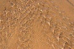 Vatten som flödar över sand som bildar den invecklade modellen Arkivbilder