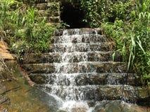 Vatten som flödar till och med det klarade av hålet royaltyfria bilder