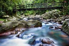 Vatten som flödar under en bro fotografering för bildbyråer
