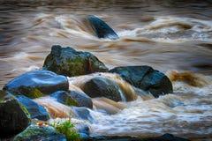 Vatten som fylls med bottensatsflöden över, vaggar Arkivbilder