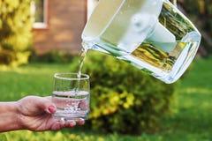 Vatten som häller från ett filter till det fria för ett exponeringsglas royaltyfri fotografi