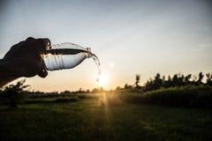 Vatten som häller på solnedgången Fotografering för Bildbyråer