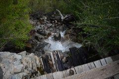 Vatten som kör under en liten träfotbro arkivfoto