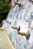 Vatten som kommer ut ur rör i en springbrunn Arkivbild