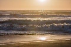 Vatten som kraschar på strandsolnedgång Royaltyfria Foton