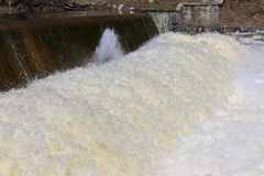 Vatten som rasar över fördämningen Arkivfoto
