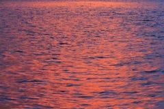 Vatten som reflekterar den röda himlen Arkivfoto
