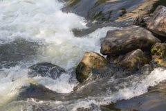 Vatten som rusar över små stenblock Royaltyfria Bilder