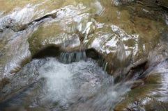 Vatten som rusar över stenen Fotografering för Bildbyråer