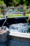 Vatten som strömmar från springbrunnen i den engelska trädgården Royaltyfri Foto