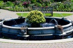 Vatten som strömmar från springbrunnen i den engelska trädgården Arkivfoto