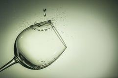 Vatten tappar att plaska på vinexponeringsglas Royaltyfria Bilder