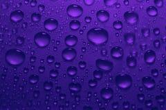 Vatten tappar på blå violett färgbakgrundstextur Arkivbilder