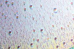 Vatten tappar på dvdmassmedia, vattendroppar på färgrik bakgrund royaltyfri bild