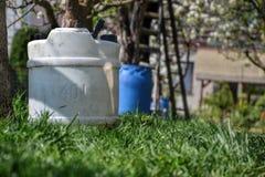 Vattenbehållare för att bevattna gräset Behållare som behåller regnvatten i trädgården Vit plast- bensindunk Gal.vattenreserv Arkivfoton
