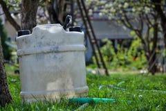 Vattenbehållare för att bevattna gräset Behållare som behåller regnvatten i trädgården Vit plast- bensindunk Gal.vattenreserv Royaltyfri Bild