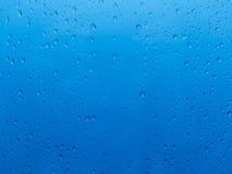 Vattendroppar över blått Arkivbild