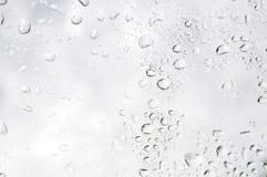 Vattendroppar för regnig dag på fönster - små droppar arkivfoto