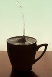 Vattendroppar i kopp kaffe Arkivfoton